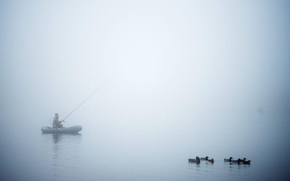 Velikiy Novgorod, Russia: un pescatore su un fiume di nebbia