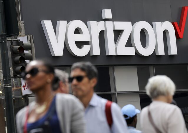 In this Tuesday, May 2, 2017 photo, people walk past a Verizon store in Manhattan's midtown area, in New York
