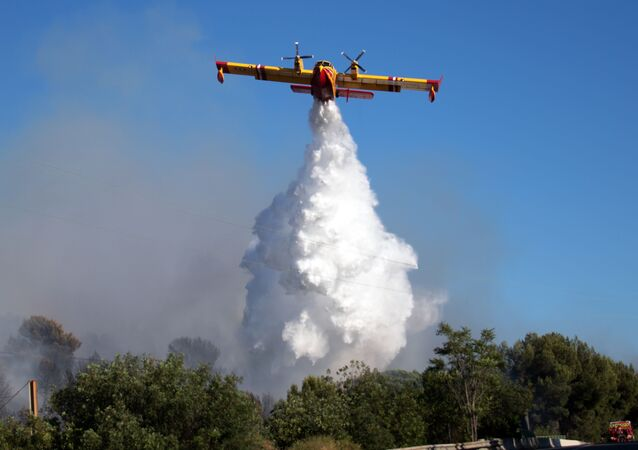 A Canadair firefighting plane drops water over a fire which broke out in the industrial zone of Vitrolles, southeastern France, on July 10, 2019.
