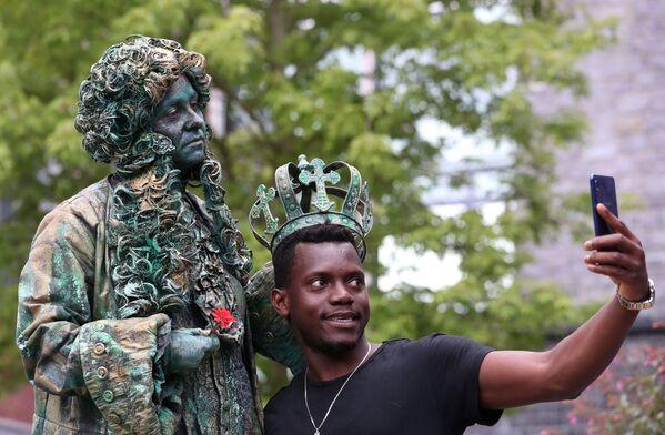 Un uomo si fa una foto con un artista del Festival Statues en Marche. - Sputnik Italia