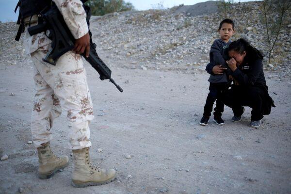 Migrante guatemaliano Lety Perez con il suo figlio supplicano il militare di far passare il confine con gli Usa. - Sputnik Italia