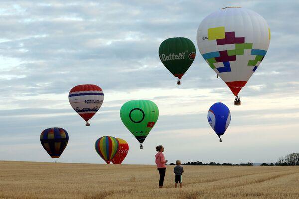 Una mamma insieme a suo figlio osservano ammirati lo spettacolo delle mongolfiere in volo. - Sputnik Italia