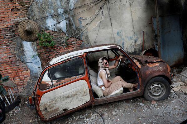 Una ragazza scatta delle foto in una macchina vecchia a Bangkok, in Thailandia. - Sputnik Italia