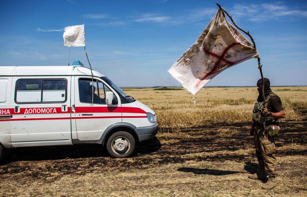 Donbass, un soldato ucraino espone la bandiera bianca al passaggio di un'ambulanza.