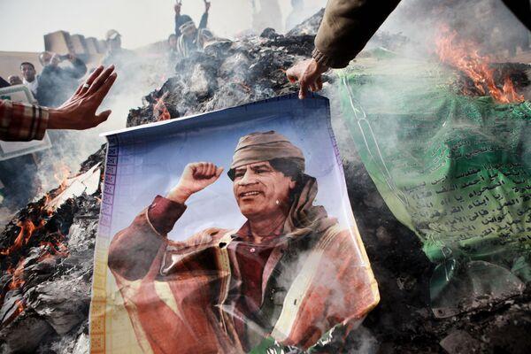 Abitanti di Bengasi bruciano i ritratti di Gheddafi. - Sputnik Italia
