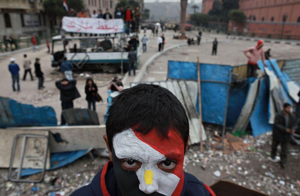 Un oppositore egiziano con il viso dipinto nei colori della bandiera egiziana sulle barricate di piazza Tahir al Cairo.