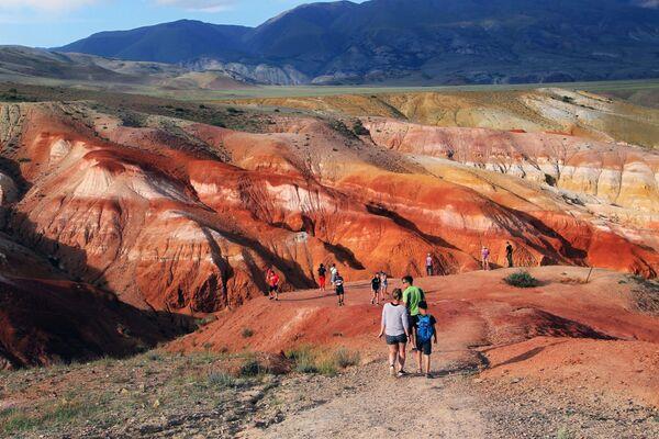 Turisti in cammino lungo la strada che conduce alla valle rossa di Kyzyl-Chin: per raggiungerla dal villaggio più vicino, Ortolyk, bisogna percorrere 21 km (gli ultimi 7 dei quali sterrati)  - Sputnik Italia