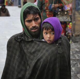 Un uomo di etnia Kashmir protegge suo figlio dal freddo a Srinagar, nel Kashmir controllato dall'India