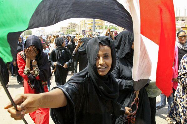 Una giovane sudanese sventola la bandiera del suo paese in segno di gioia per la firma dell'accordo tra il Consiglio dei militari ed il Fronte nazionale di liberazione del paese, dopo sette mesi di violenti scontri - Sputnik Italia