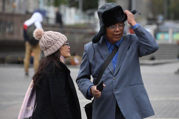 Turisti stranieri con colbacchi e cappelli invernali a Mosca, dove il 5 agosto 2018 è stato il giorno più freddo da quando esistono le misurazioni: la temperatura minima nella notte ha toccato soltanto 6° gradi centigradi - Sputnik Italia
