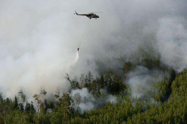 Un elicottero Mil Mi-8 dei vigili del fuoco russi in volo sopra i boschi in fiamme della regione di Krasnoyarsk, in Siberia - Sputnik Italia