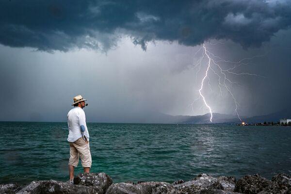 Un uomo osserva un fulmine che si abbatte sul lago di Ginevra, in Svizzera  - Sputnik Italia