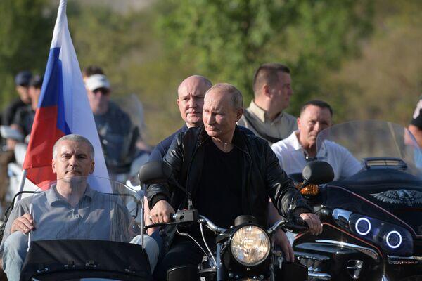 Il presidente russo Putin a bordo di una moto Ural con sidecar saluta i partecipanti al motoraduno organizzato dal club Lupi della Notte a Sebastopoli in Crimea - Sputnik Italia
