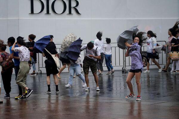 Passanti sorpresi dalle piogge causate dal tifone Lekima a Shangai, in Cina - Sputnik Italia