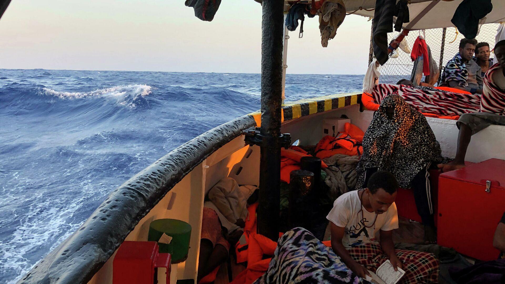 Мигрант читает Коран на борту судна испанских спасателей Open Arms в Средиземном море - Sputnik Italia, 1920, 27.05.2021