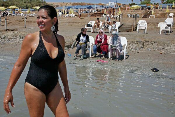 Una donna in costume da bagno nella spiaggia di Kalya Beach, vicino alla città di Gerico. Sullo sfondo donne palestinesi chiaccherano sedute. - Sputnik Italia