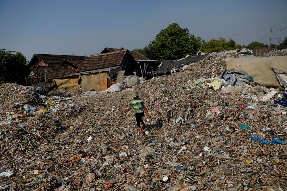 Un bambino a spasso sopra una distesa di rifiuti