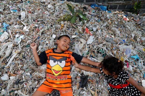 Questi bambini giocano sopra un cumulo di rifiuti - Sputnik Italia