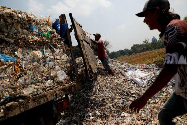 Due abitanti di Bangun impegnati a scaricare i rifiuti di una cartiera nel villaggio di Bangun, nella provincia di Mojokerto, in Indonesia - Sputnik Italia