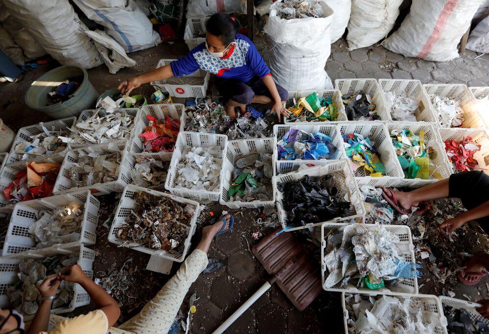 Una donna separa plastica e rottami nel centro di raccolta dei rifiuti di Mojokerto