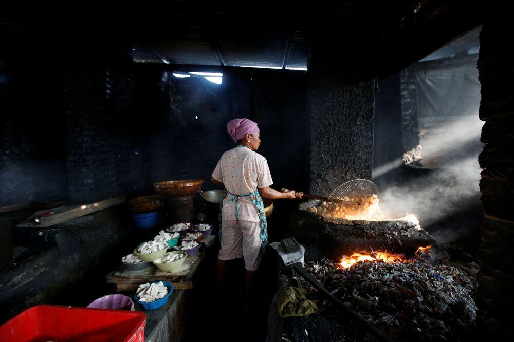 Questa donna prepara da mangiare sopra ad un fuoco ricavato dalla combustione dei rottami