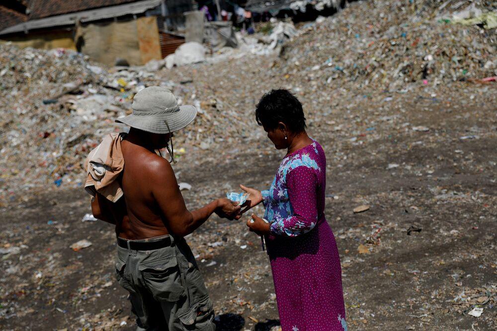 Una donna riceve la sua paga giornaliera per aver lavorato nella discarica