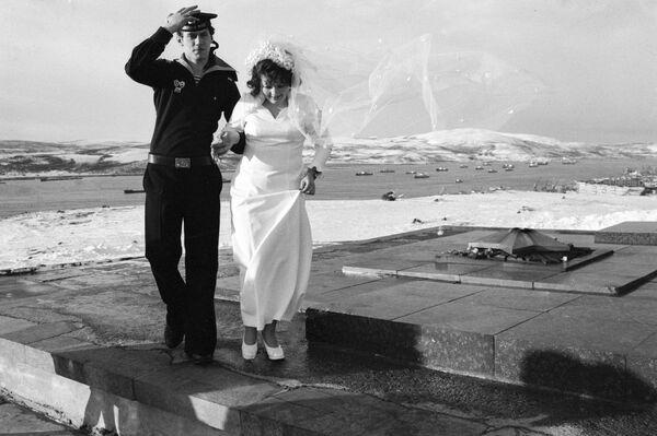 Novelli sposi presso il monumento dedicato ai difensori del Circolo Polare Artico a Murmansk. 1977. - Sputnik Italia