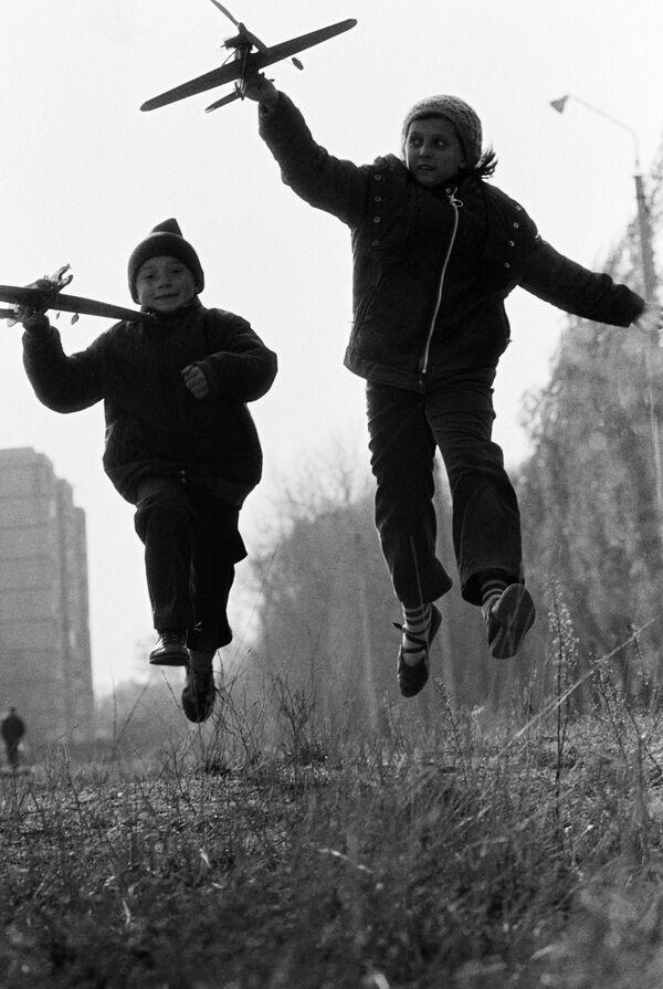 Bambini giocano con gli aeroplanini. 1988. - Sputnik Italia