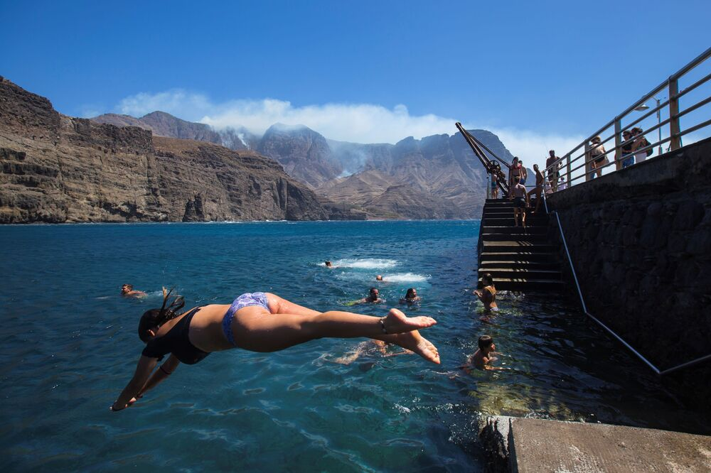 Una bagnante in una spiaggia dell'isola di Gran Canaria, colpita da incendi boschivi.