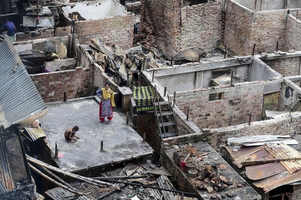 Un bambino gioca sul tetto di un'edificio disrutto dall'incendio in baraccopoli di Dhaka, in Bangladesh.