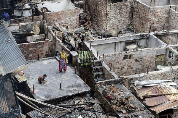 Un bambino gioca sul tetto di un'edificio disrutto dall'incendio in baraccopoli di Dhaka, in Bangladesh. - Sputnik Italia