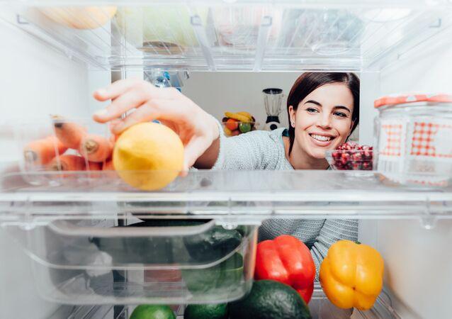 Ragazza prende un limone dal frigorifero