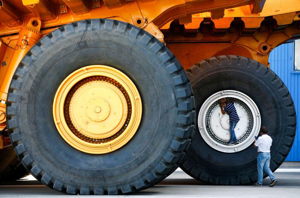 Una foto ricordo vicino alle ruote giganti di un'escavatrice BelAZ a Zhodino, in Bielorussia.