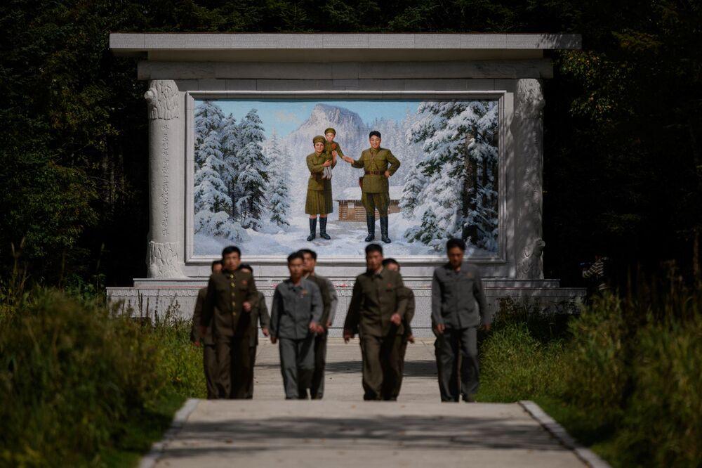 Visitatori davanti all'affresco raffigurante il defunto leader nordcoreano Kim Il Sung, con moglie e figlio, all'ingresso del 'Campo segreto'.