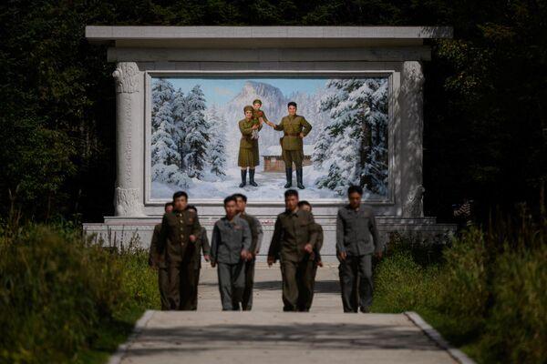 Visitatori davanti all'affresco raffigurante il defunto leader nordcoreano Kim Il Sung, con moglie e figlio, all'ingresso del 'Campo segreto'. - Sputnik Italia
