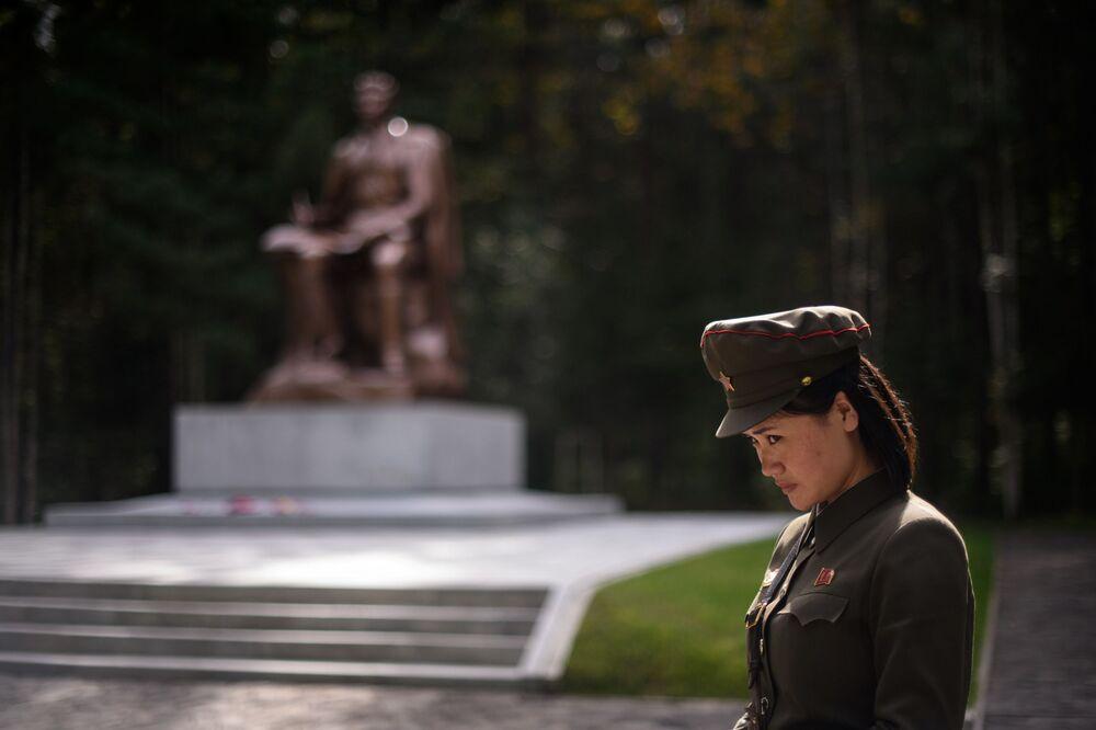 La guida turistica davanti alla statua del defunto leader nordcoreano Kim Il Sung.