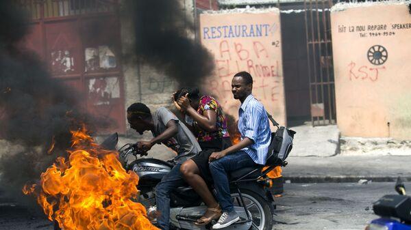 Мото-такси проезжающее мимо горящей шины в Порт-о-Пренсе, Гаити - Sputnik Italia