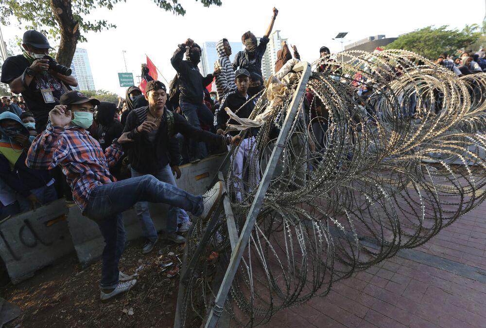 I manifestanti lanciano fumogeni contro la polizia, pietre e cercano di rimuovere le barriere della polizia dalle strade