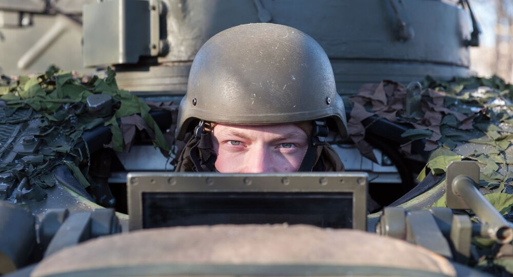 A soldier looking out of the British armed reconnaissance vehicle FV107 SCIMITAR during a NATO demonstration of military vehicles and weapons in Latvia.
