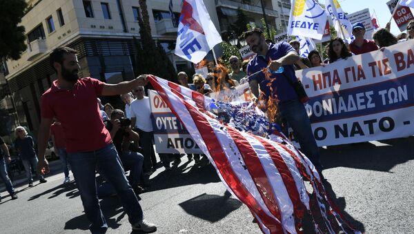 Manifestanti greci bruciano la bandiera americana durante una manifestazione il 5 ottobre 2019 - Sputnik Italia