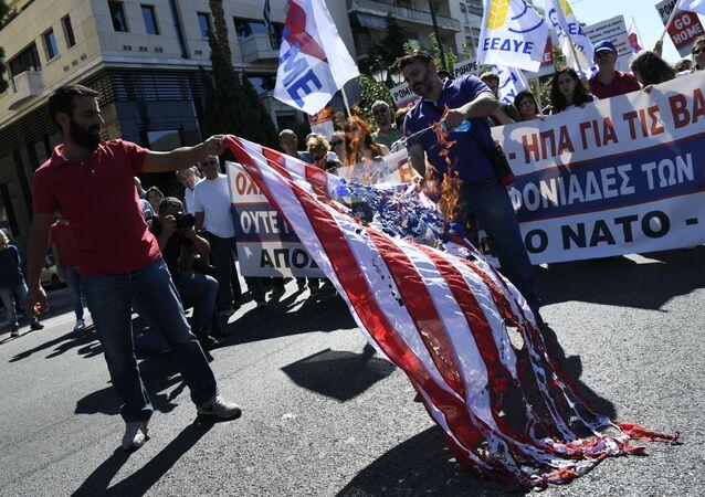 Manifestanti greci bruciano la bandiera americana durante una manifestazione il 5 ottobre 2019