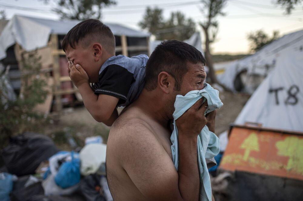 Uomo con in collo un bambino durante gli scontri vicino al campo di rifugiati Moria all'isola greca Lesbo.