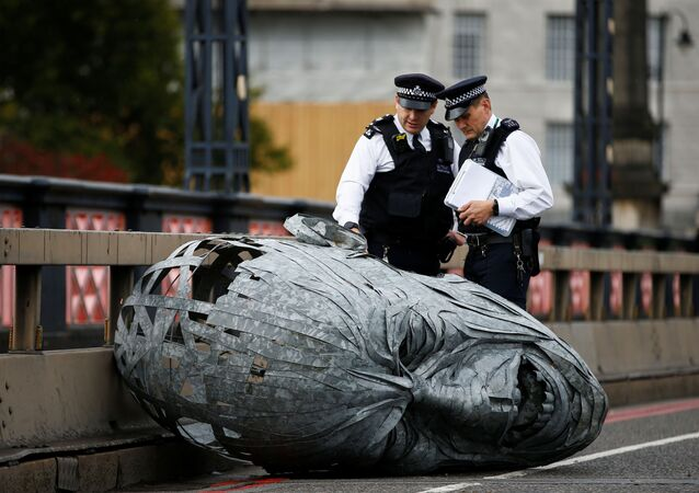 Police officers look at a sculpture made by activists at Lambeth Bridge during the Extinction Rebellion protest in London, Britain October 7, 2019