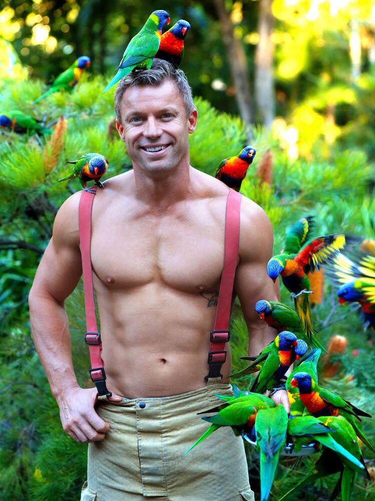 Il vigile del fuoco Aaron posa insieme a degli uccelli per la versione Foresta del calendario degli Australian Firefighters
