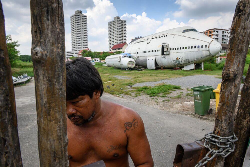 Un uomo al cancello, dietro un aereo abbandonato in un sobborgo di Bangkok.