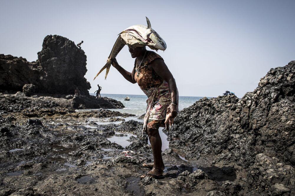 Una donna porta pesci sventrati in testa a Porto Mosquito, Capo Verde.