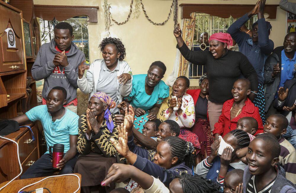 Madre, amici e vicini di casa atleta keniota Eliud Kipchoge guardano la maratona in cui Eliud Kipchoge ha stabilito il nuovo record del mondo.