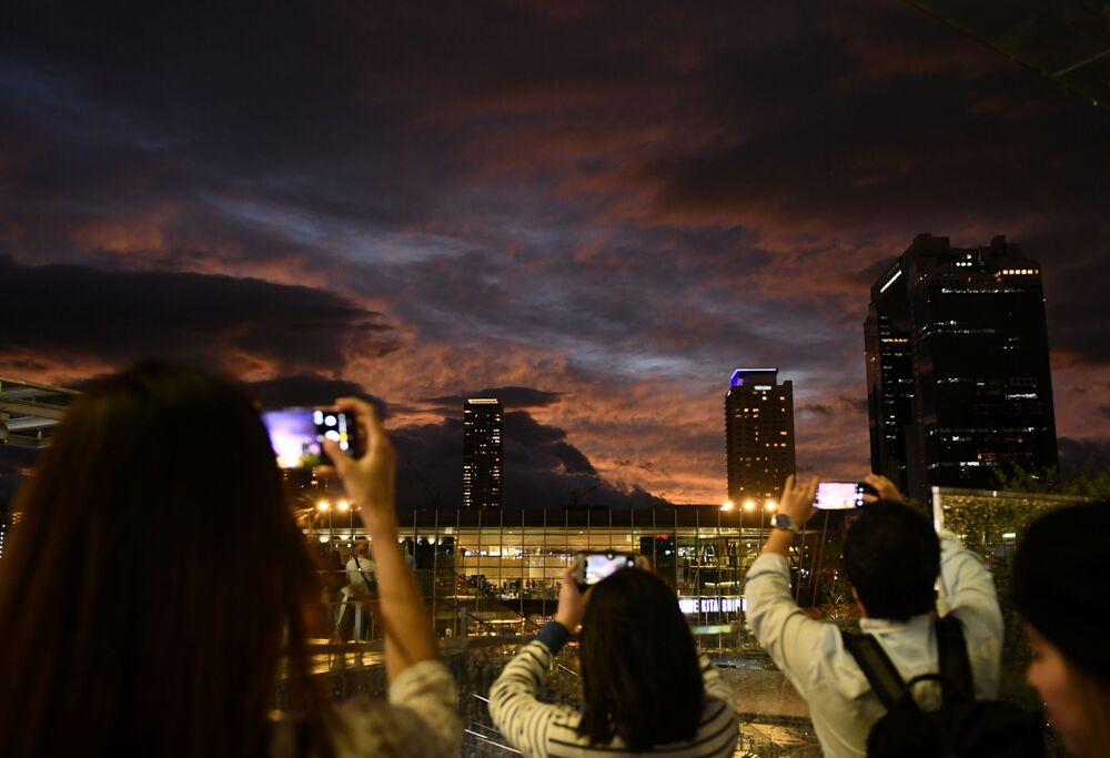 Cittadini di Osaka fotografano il cielo al tramonto mentre il tifone Habigis si avvicina.