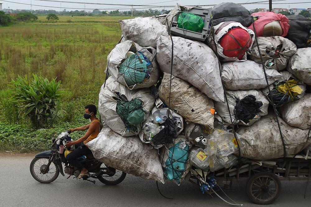 Vietnam, un uomo trasporta un voluminoso carico di rifiuti di plastica da rivendere