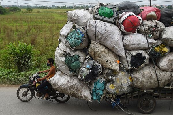 Vietnam, un uomo trasporta un voluminoso carico di rifiuti di plastica da rivendere - Sputnik Italia